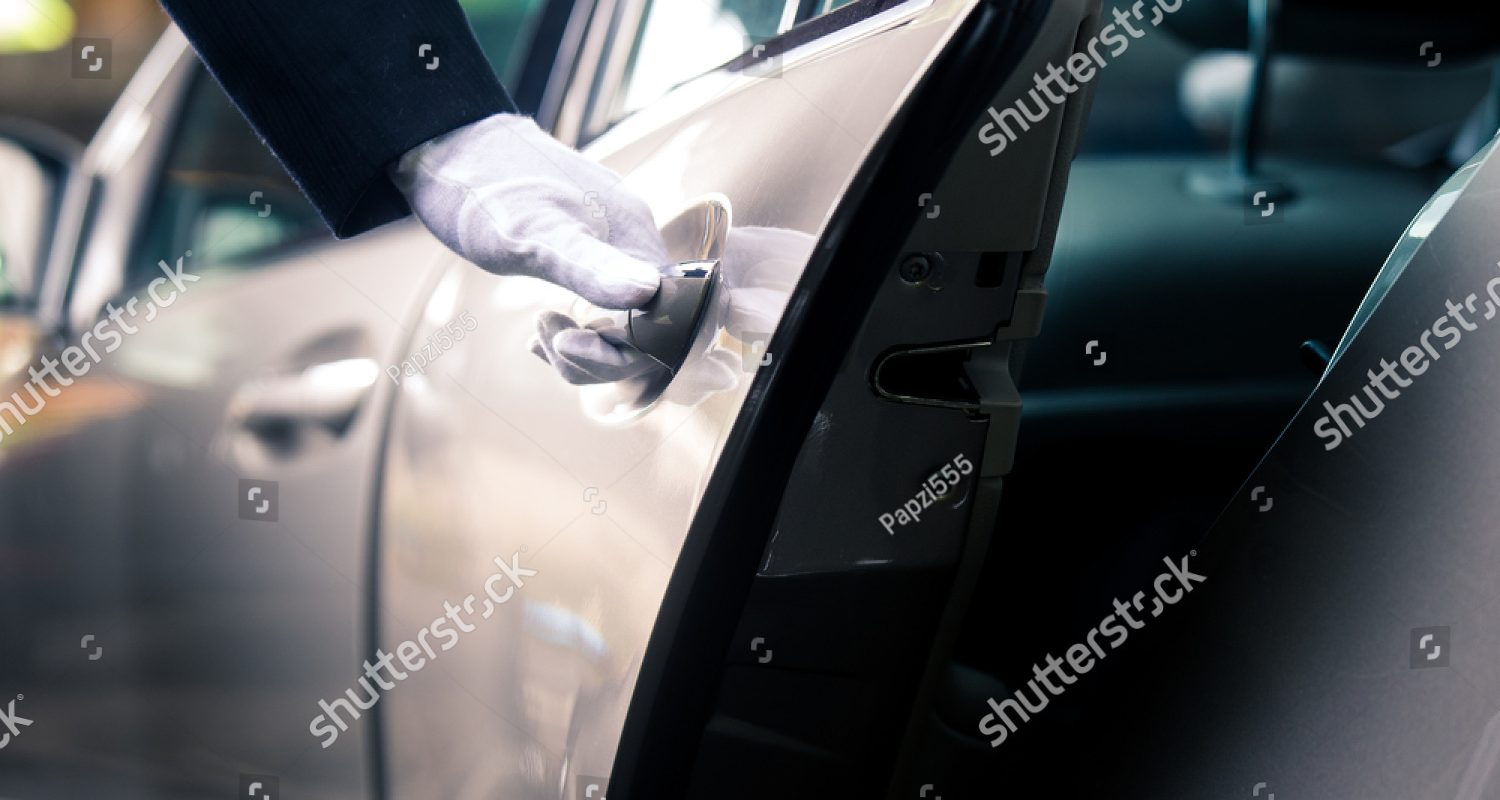 stock-photo-closeup-of-chauffeur-opening-car-door-with-glove-707662543